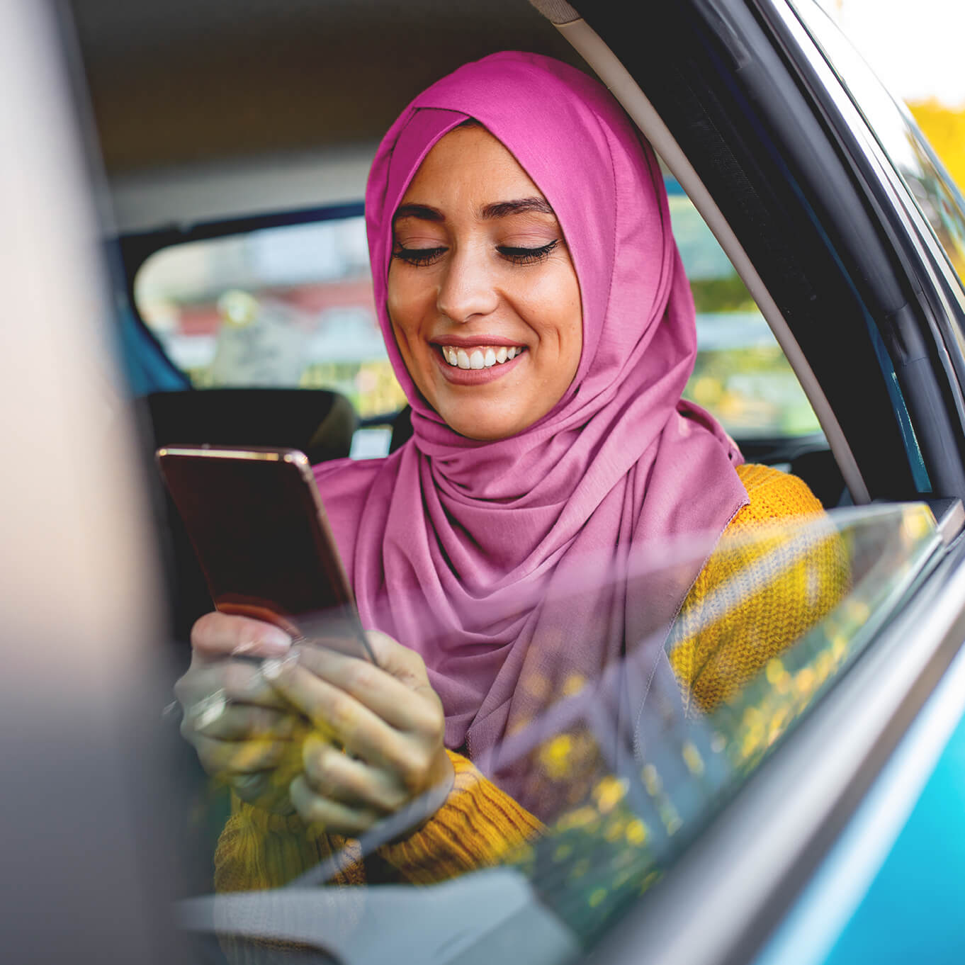 Smiling young woman wearing a yellow knit sweater and pink hijab looking at her mobile phone while seated in the back of a car.