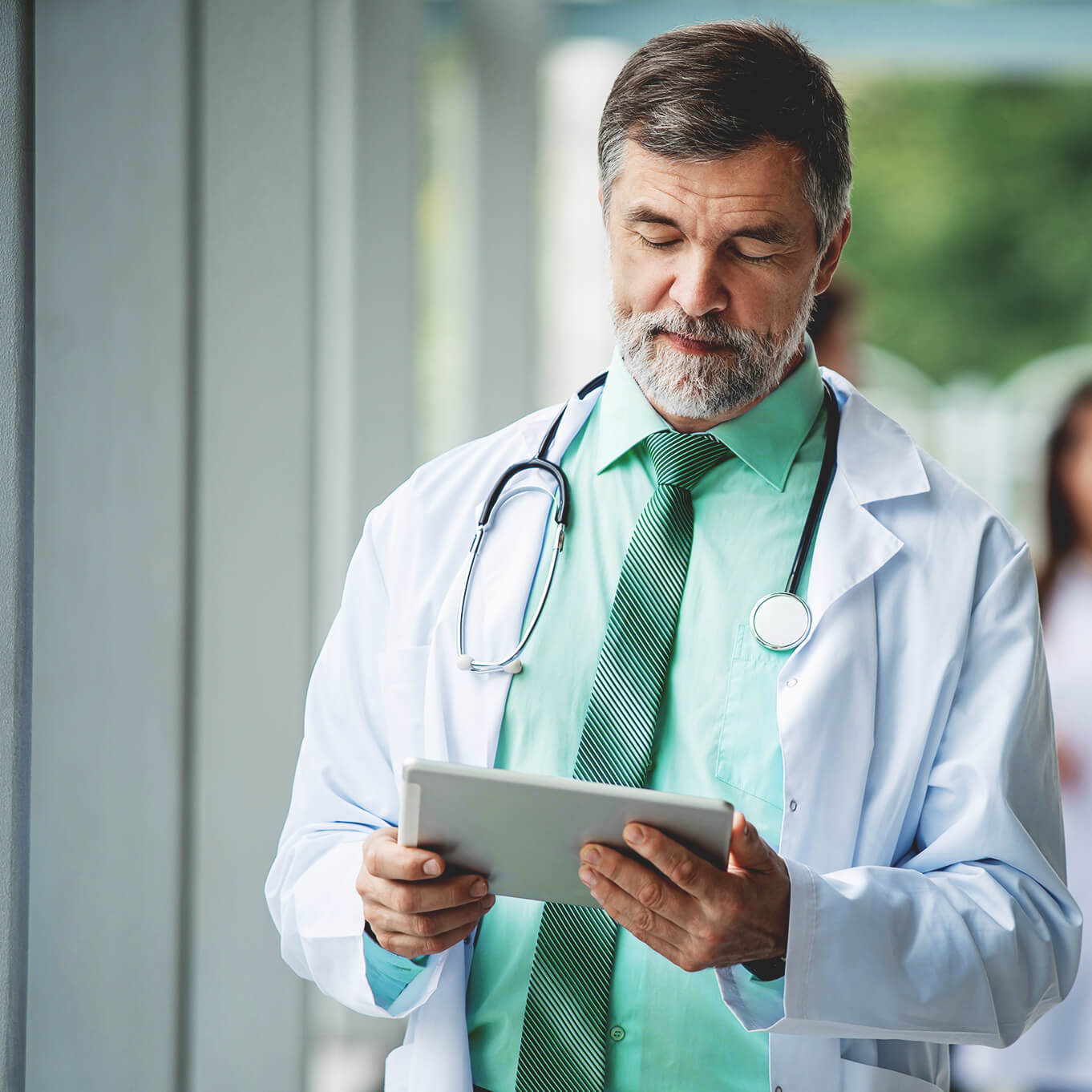 Mature doctor in a light green shirt and white lab coat, with a stethoscope hanging around his neck. He looks intently at a digital tablet.