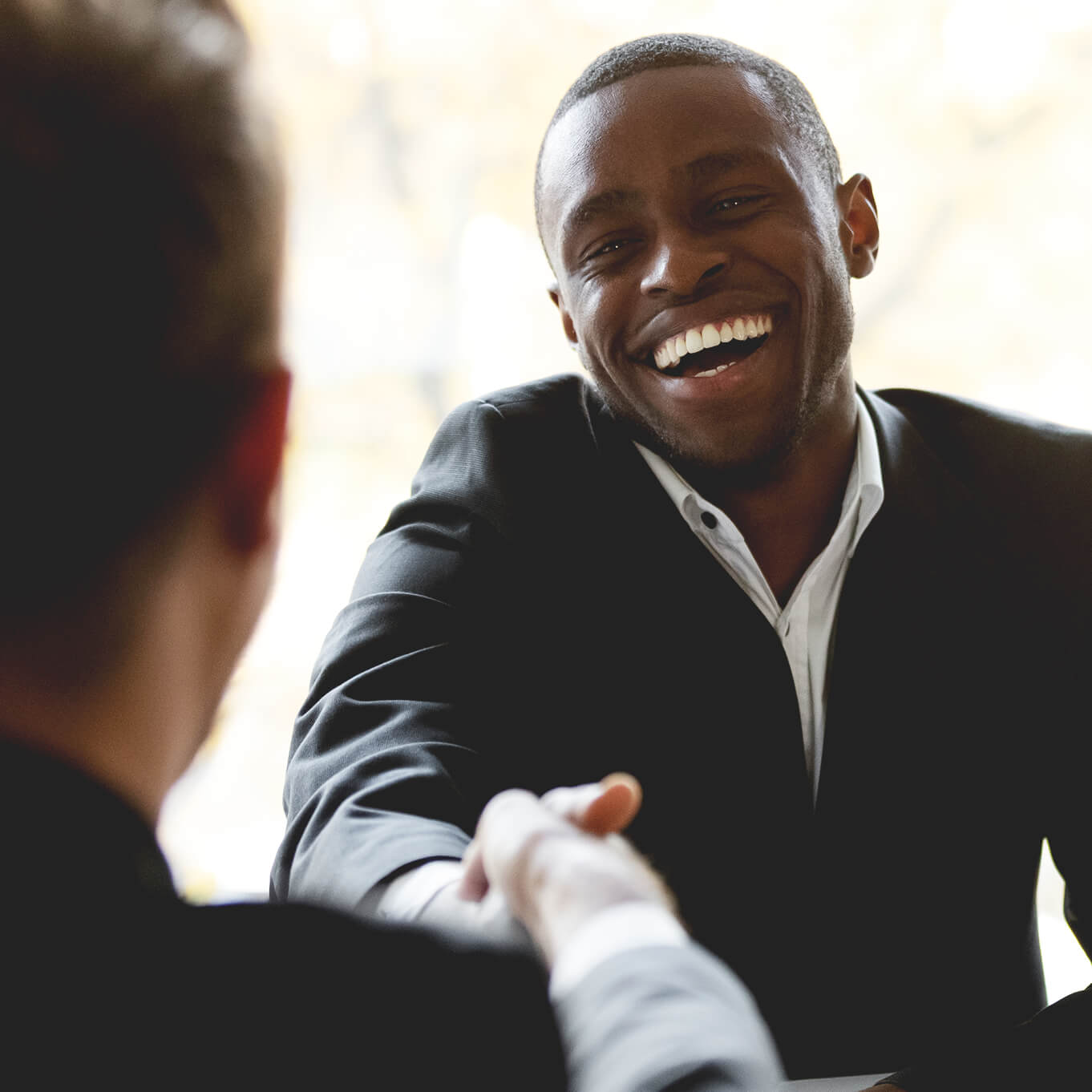 Happy businessman with a big smile, wearing a black suit jacket and shaking hands with another person.