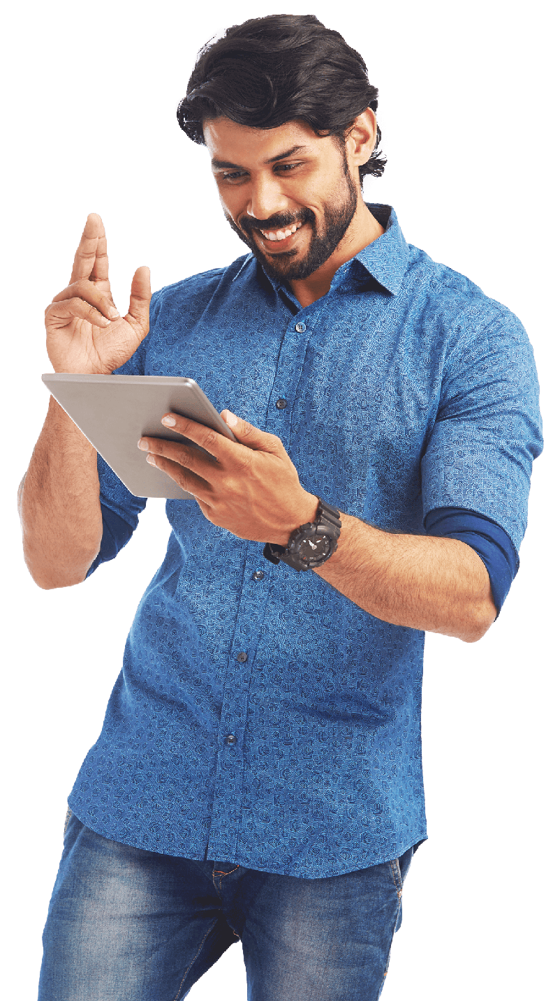 Happy man with a broad grin and shaggy dark brown hair in a blue shirt looking at the tablet he holds in his left hand.