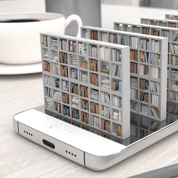 A smartphone laying on a table that has been edited to make it appear that shelves of books are coming out of the screen.