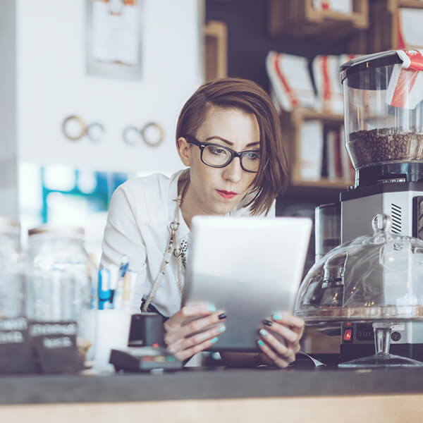 Young barista leaning on a counter,  looking over her digital tablet with an expression of deep concentration on her face.