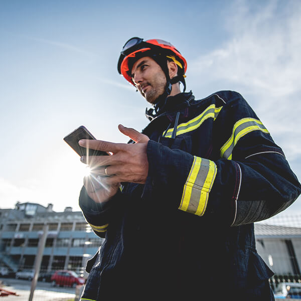 Firefighter in a bright orange helmet and navy coat with reflective yellow safety stripes, holding a smartphone.