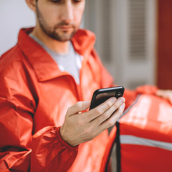 Delivery man in a red jacket with a red delivery box, looking intently at his phone.