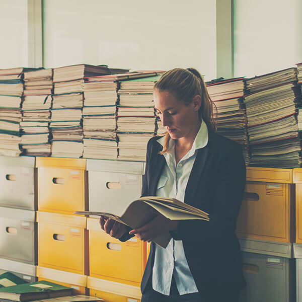 Woman standing in front of stacks of books and a large filing cabinet, reading a book.