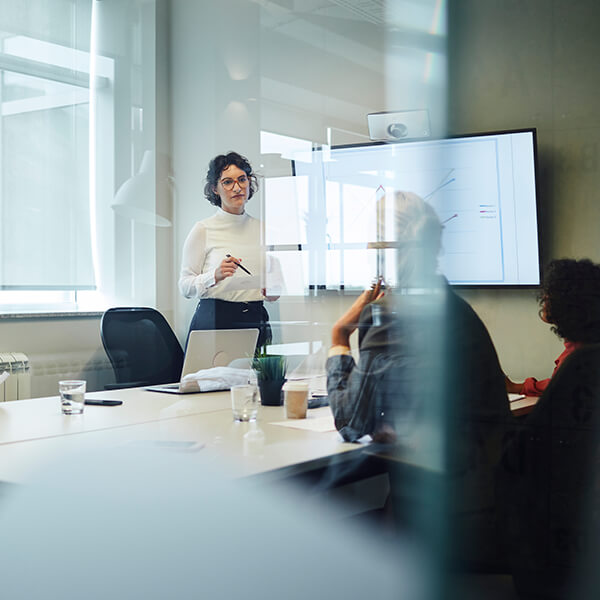 Woman standing in front of a whiteboard, talking to colleagues.