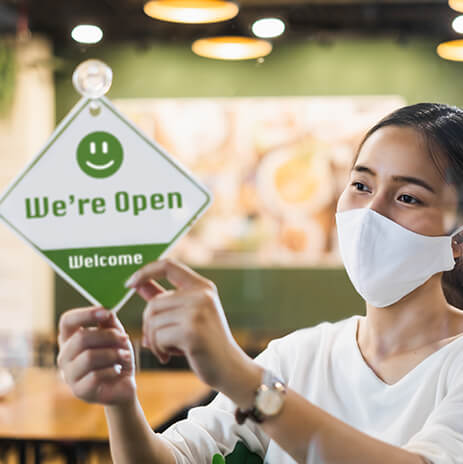 """Woman in a mask, putting an """"OPEN"""" sign on the door."""