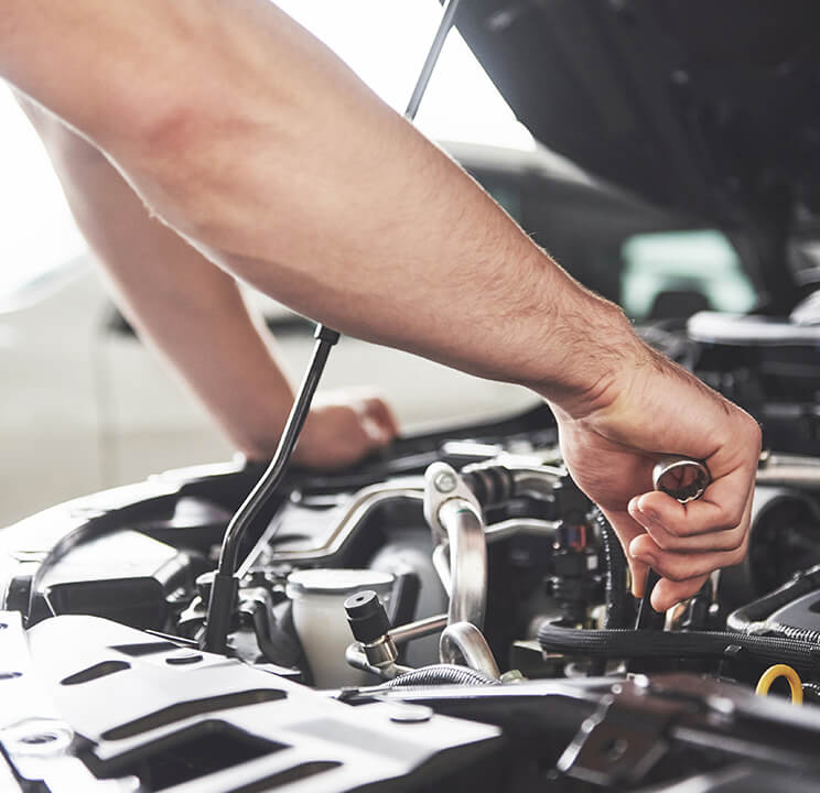 Close-up of hands holding a wrench and working on a car engine.