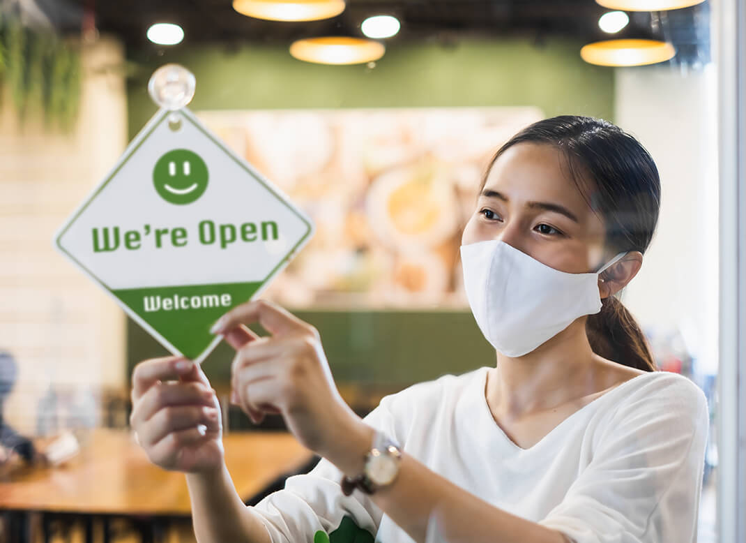 """Woman in a store wearing a face mask, flipping a sign on the door to say, """"We're Open!""""."""