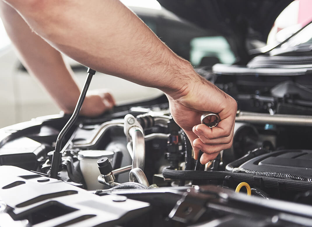 Close-up of a person's hands doing work on a car.