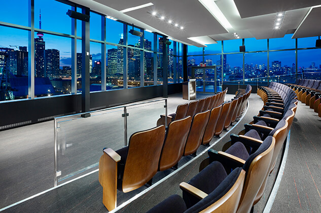 Rows of empty chairs line a room like an auditorium. The room's visible walls are lined with windows and look out over the city.
