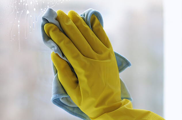 A hand in a yellow rubber glove scrubs a window with a cloth.