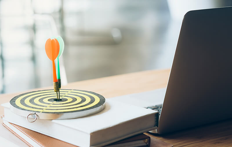 Small dartboard sitting on a desk, next to a laptop. Stuck in the center of the dartboard are a red and green dart.