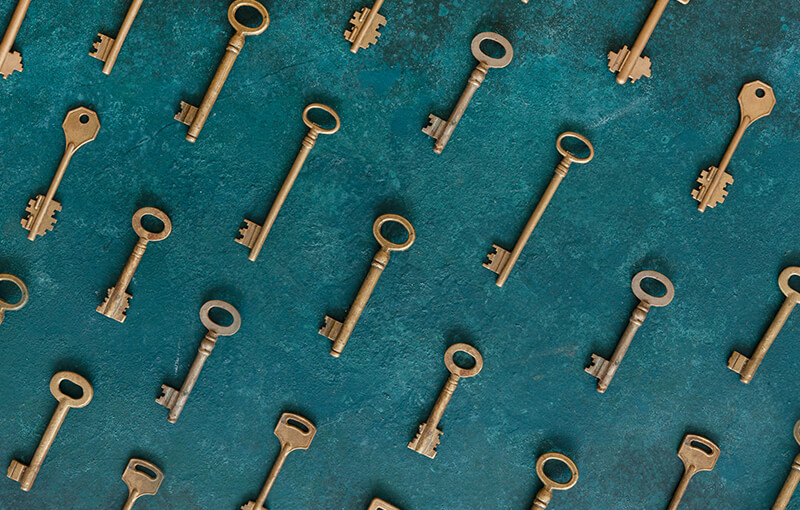 Pattern of antique gold keys laying diagonally in lines against a background painted dark teal.
