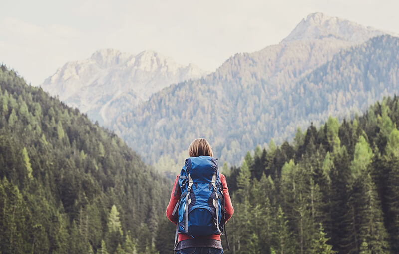 Back of a travelling woman wearing a large blue backpack, looking out over tree-covered mountains.