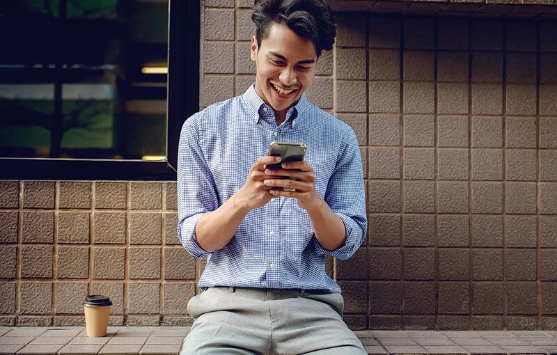 Man sitting against a tiled wall in a blue button-up shirt, smiling while looking at his mobile phone. Sitting to his left is a brown, disposable coffee cup.