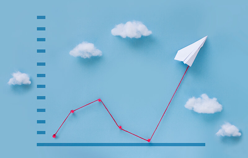 A 3D line graph showing improvement against a light blue background. The line is made of red string and at the end of the string is a paper airplane. There are five small bits of cotton representing clouds sitting against the background, making it appear that the line and paper airplane are flying off into a sky.