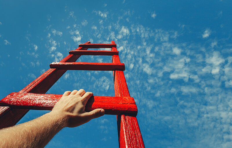 A wooden ladder painted red pointing up into a blue sky. A hand rests on the lowest rung of the ladder.