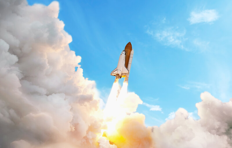 Rocket launching into a clear blue sky
