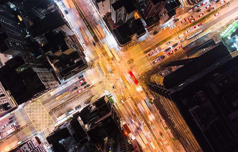 Birds-eye view of an city road intersection at night.