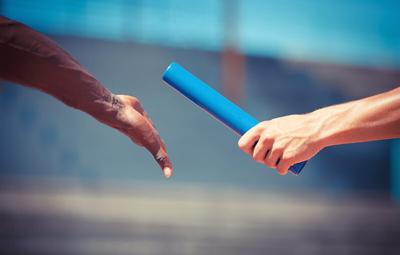 Close-up of two hands passing a relay baton.