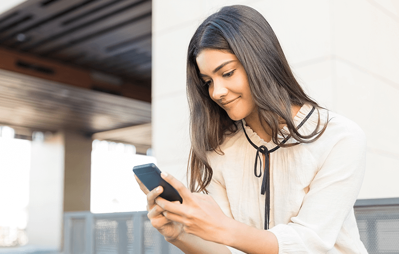 Young woman sits on steps, holding and looking at her mobile phone - Neovation Learning Solutions