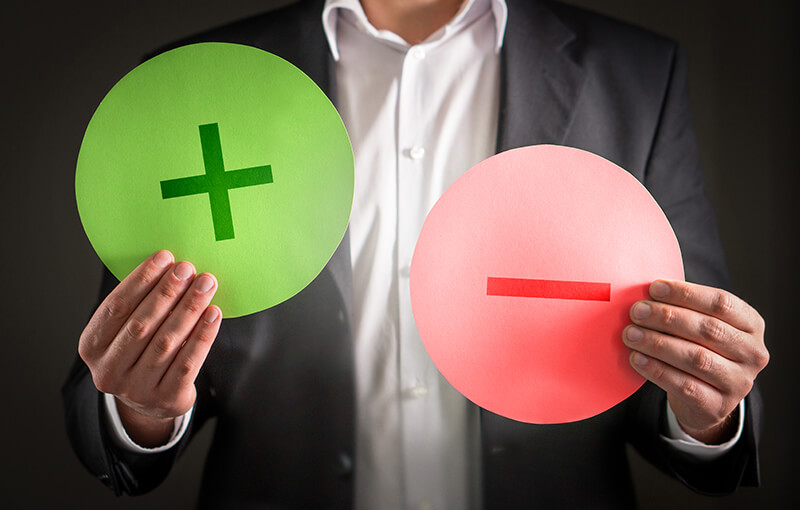 "A person holding up two circles; one is green with a ""plus"" sign and one is red with a ""minus"" sign - Neovation Learning Solutions"