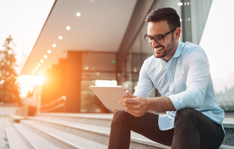 A person with short brown hair and glasses sits on the edge of some stairs in front of a large corporate building. They're smiling while they hold a tablet. - Neovation Learning Solutions