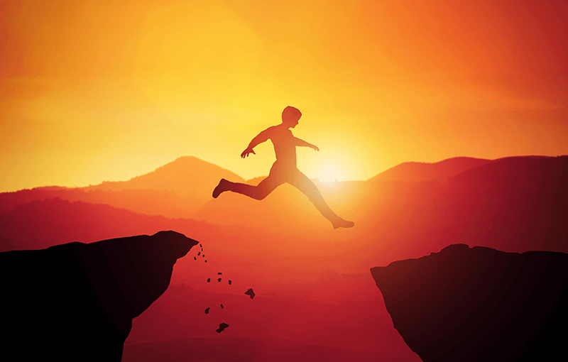 Image of a silhouetted figure jumping off a cliff across a gap to another cliff, against a sunset - Neovation Learning Solutions