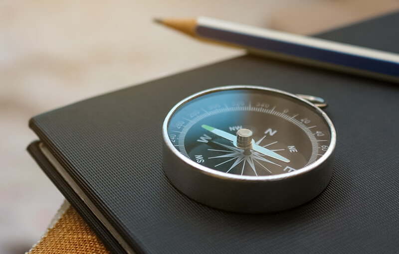 Compass resting on a black notebook with a pencil sitting beside it, slightly blurred in the background.
