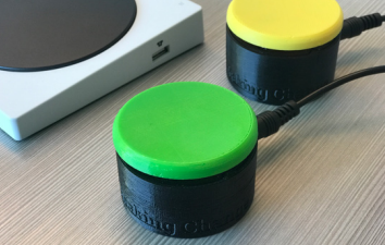 Two accessible swtiches: Short, cylindrical buttons, one with a green top, one with a yellow top.