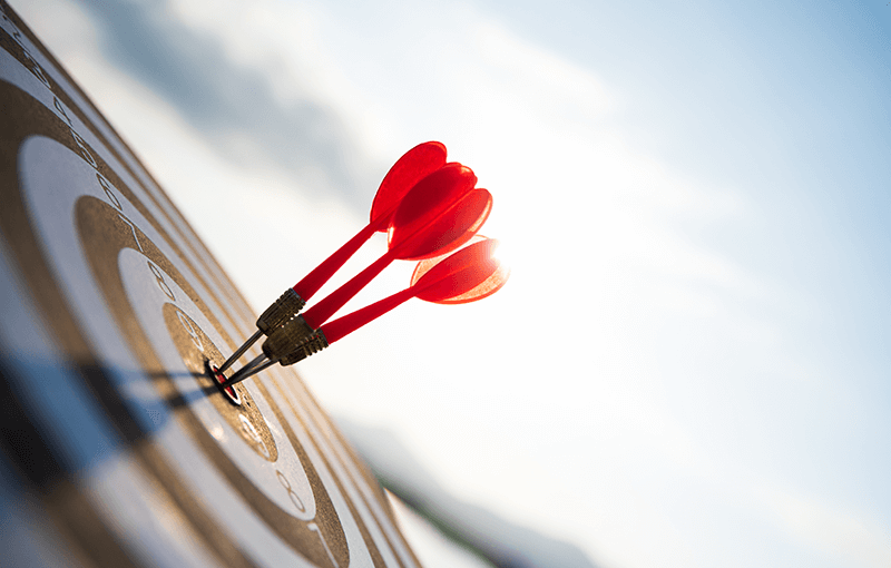 Three red darts in the center of a target, against a blue sky.