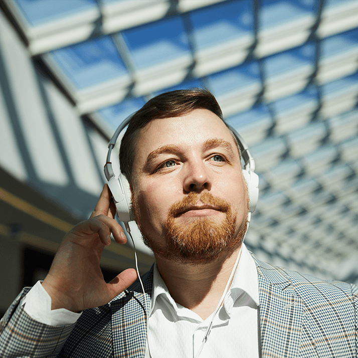 Man with short hair holding his hand to the headphones he's wearing.