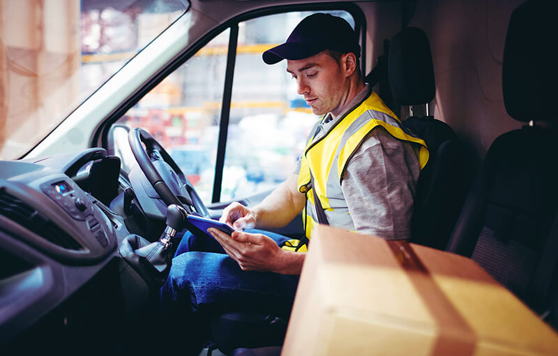 Delivery driver wearing a dark blue baseball cap and yellow safety vest, sitting in a parked car, looking at his digital tablet.