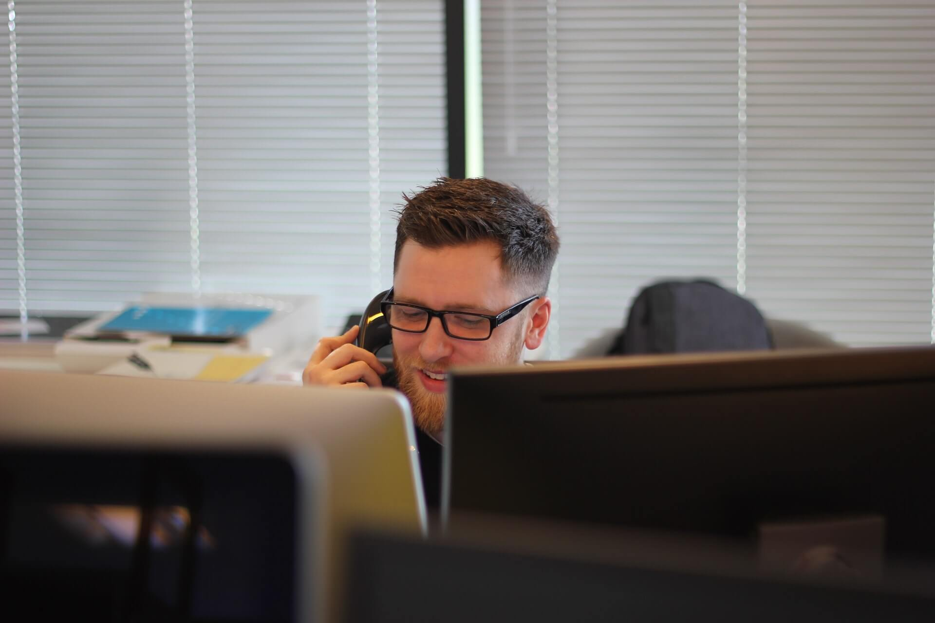 man on the phone while in front of two screens