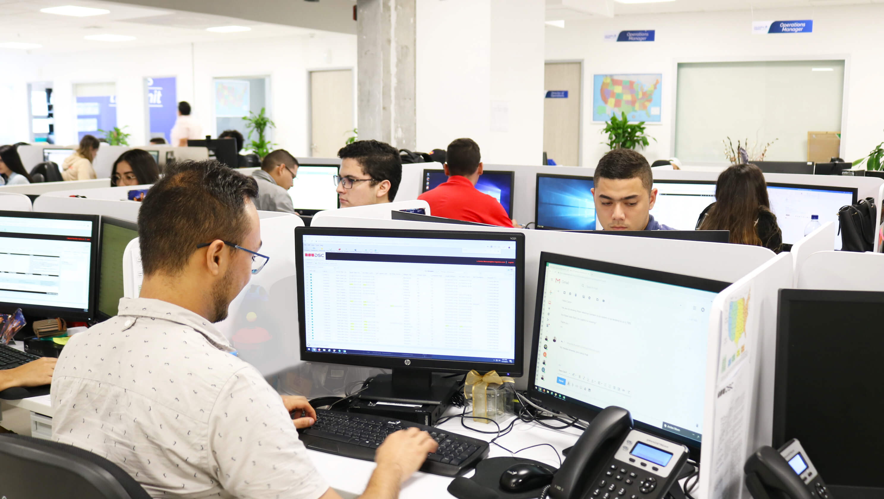 Person working on computer with other team members behind
