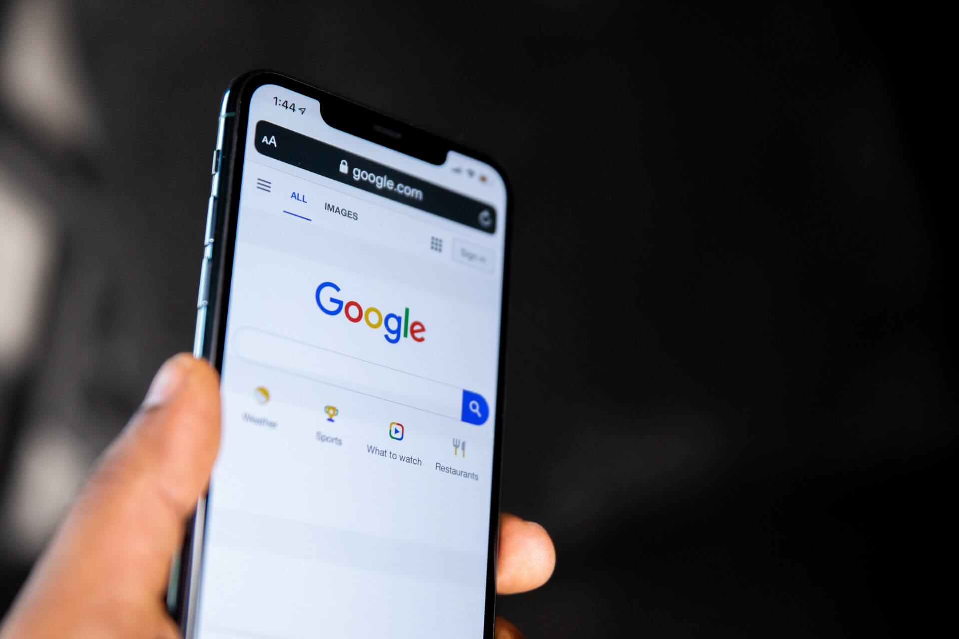 hand holding a mobile with google search on the screen