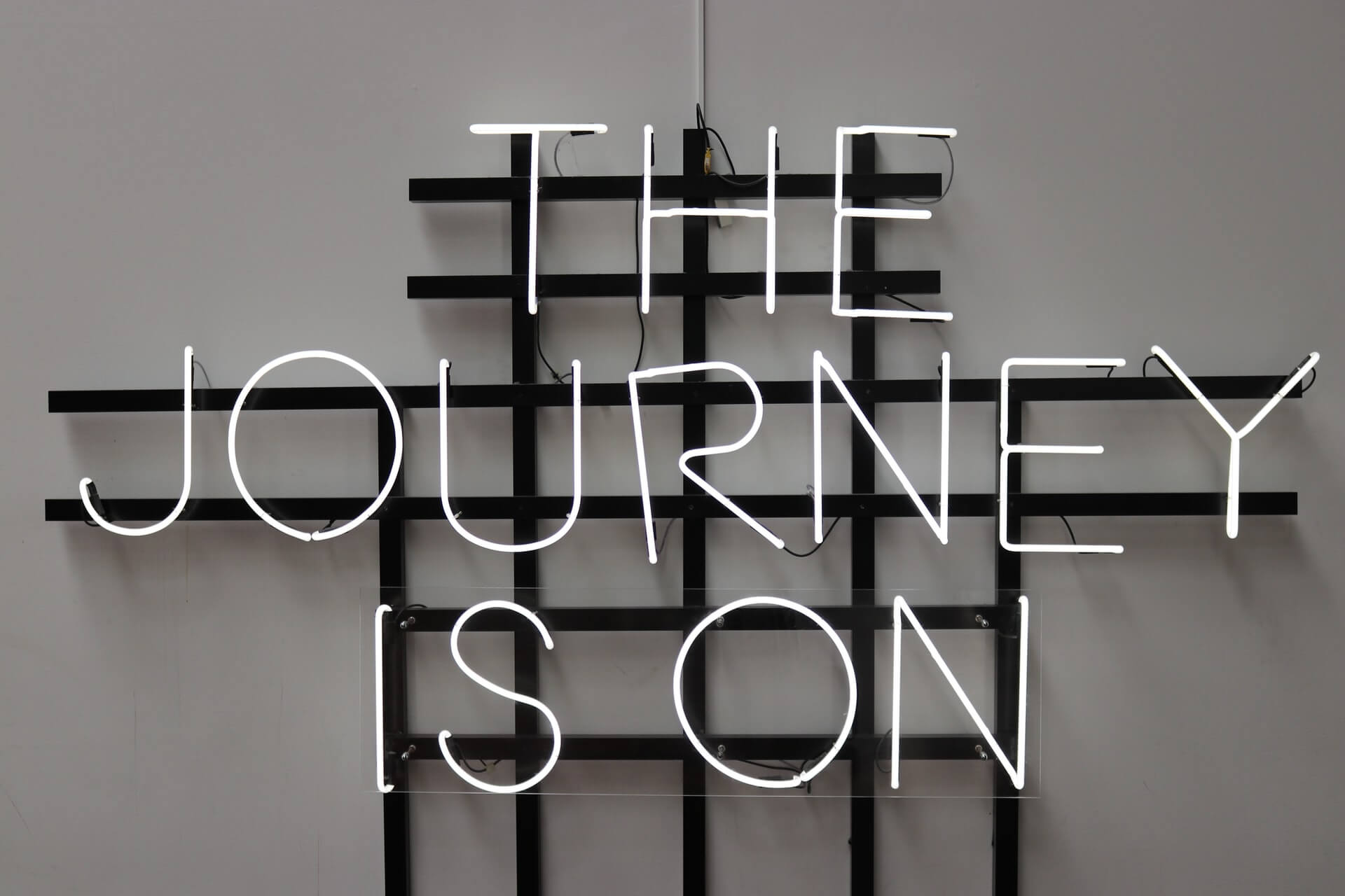 Neon sign that reads the Journey is on