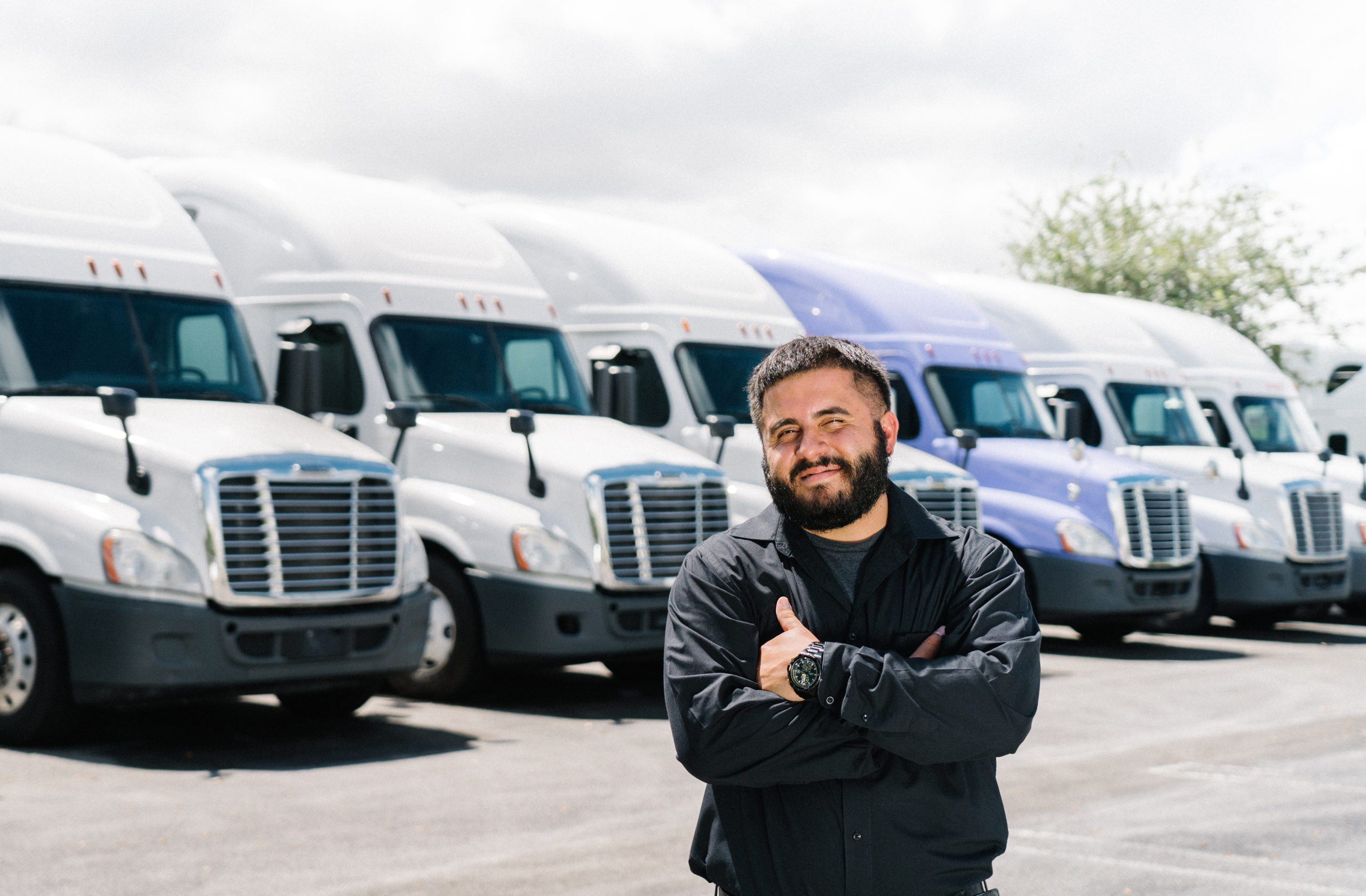 A Fleet Owner Stands in Front of Tractor Vehicles He has Listed on COOP