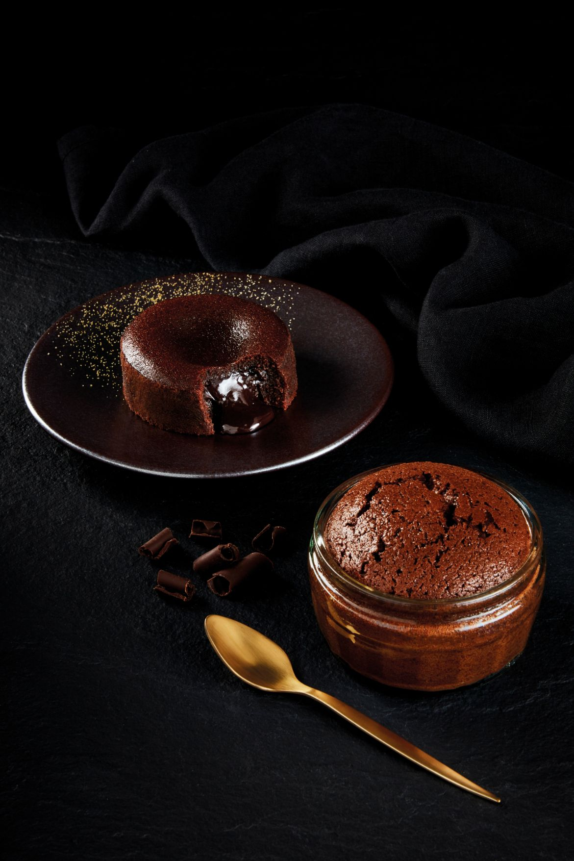 Gü Chocolate soufflé on a dark background with a gold spoon and speckled gold plate