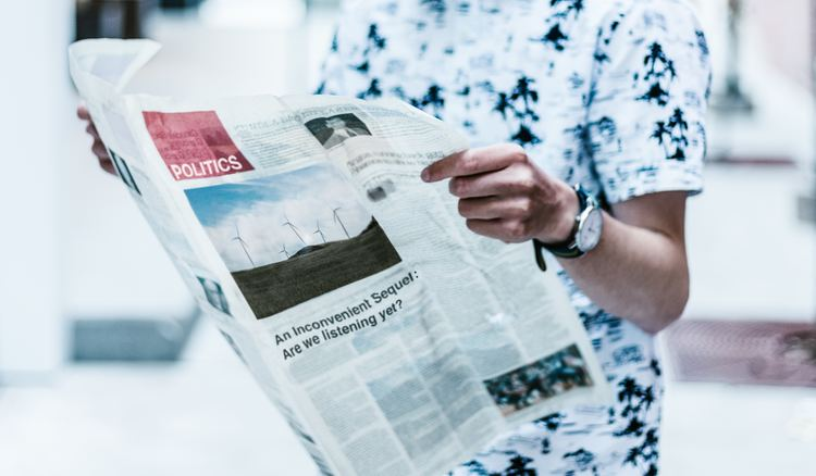 student reading newspaper for A-level results