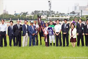 Damien Lane holds up the victorious saddle cloth number 12, picture Japan Racing Association