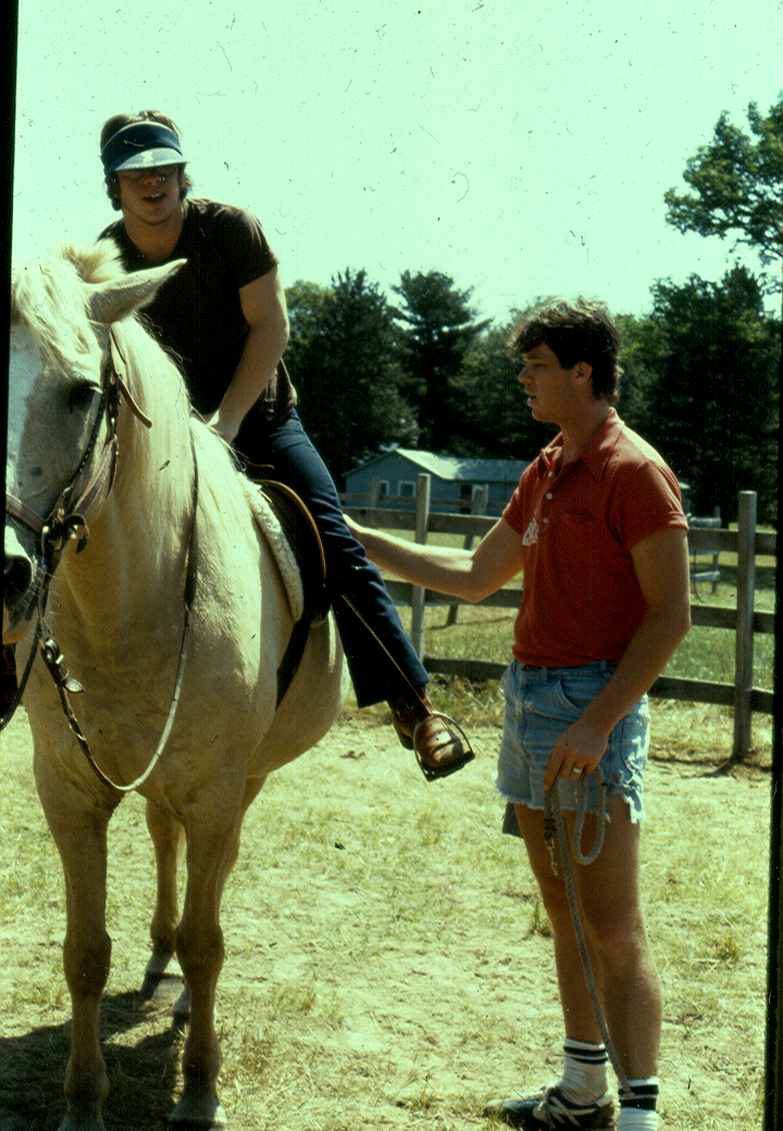 A boy sitting a top a white horse being supported by a camp counselor holding a rope.