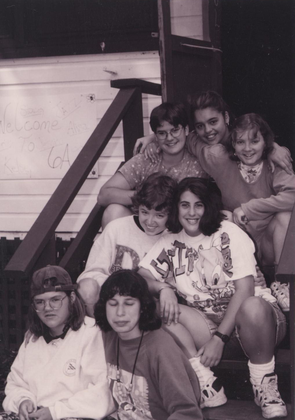 A group of campers sitting on the stairs together smiling.