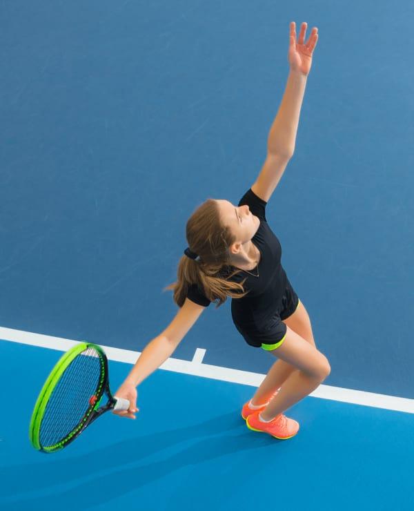 Woman serves a tennis ball on a blue tennis court