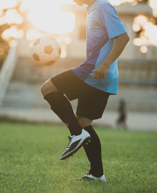 Young boy kicking a soccer ball on a pitch