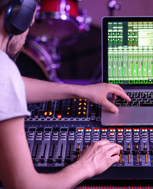 Man at a music mixing desk with headphones on