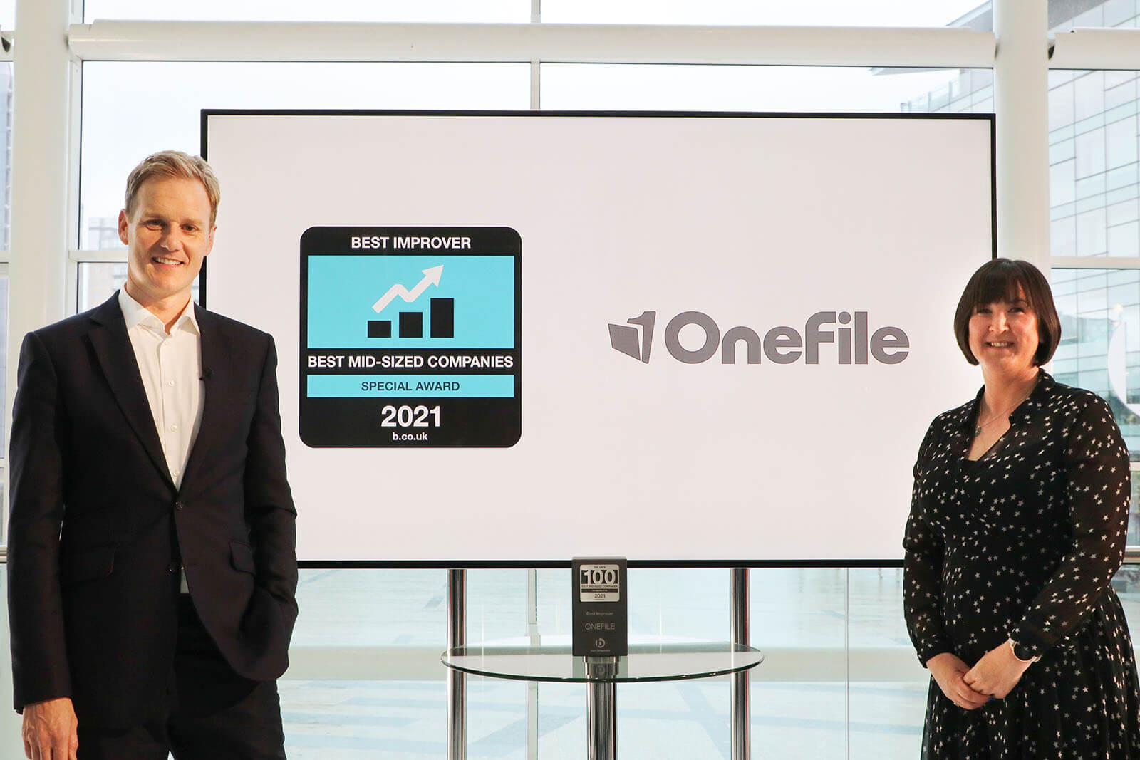 Presenter Dan Walker with the CEO and co-founder of Onefile Susanna Lawson as she recieves the Best Improver Special Award at Best Companies Live