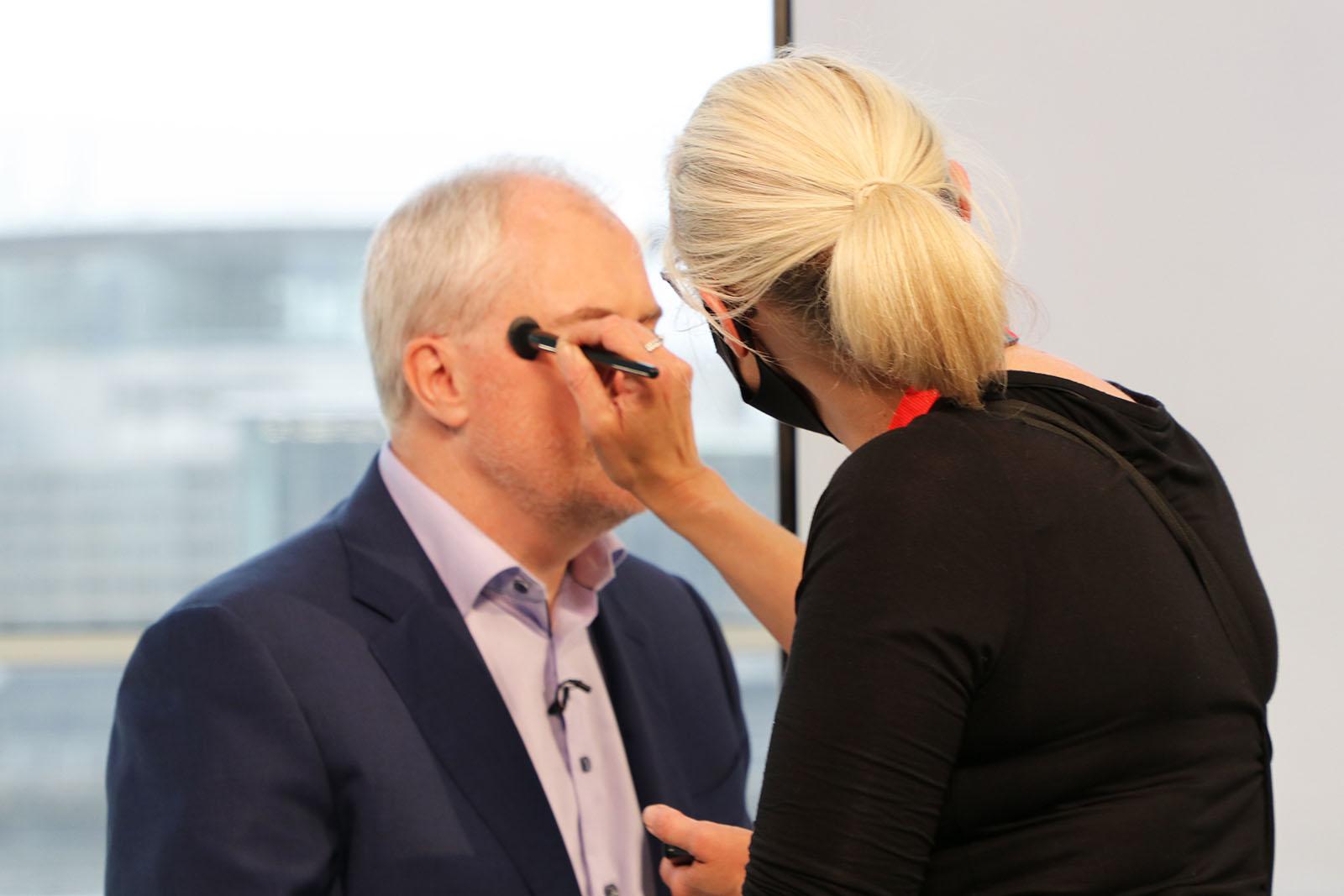 Best Companies CEO Jonathan Austin receiving makeup touchups on set at Best Companies Live