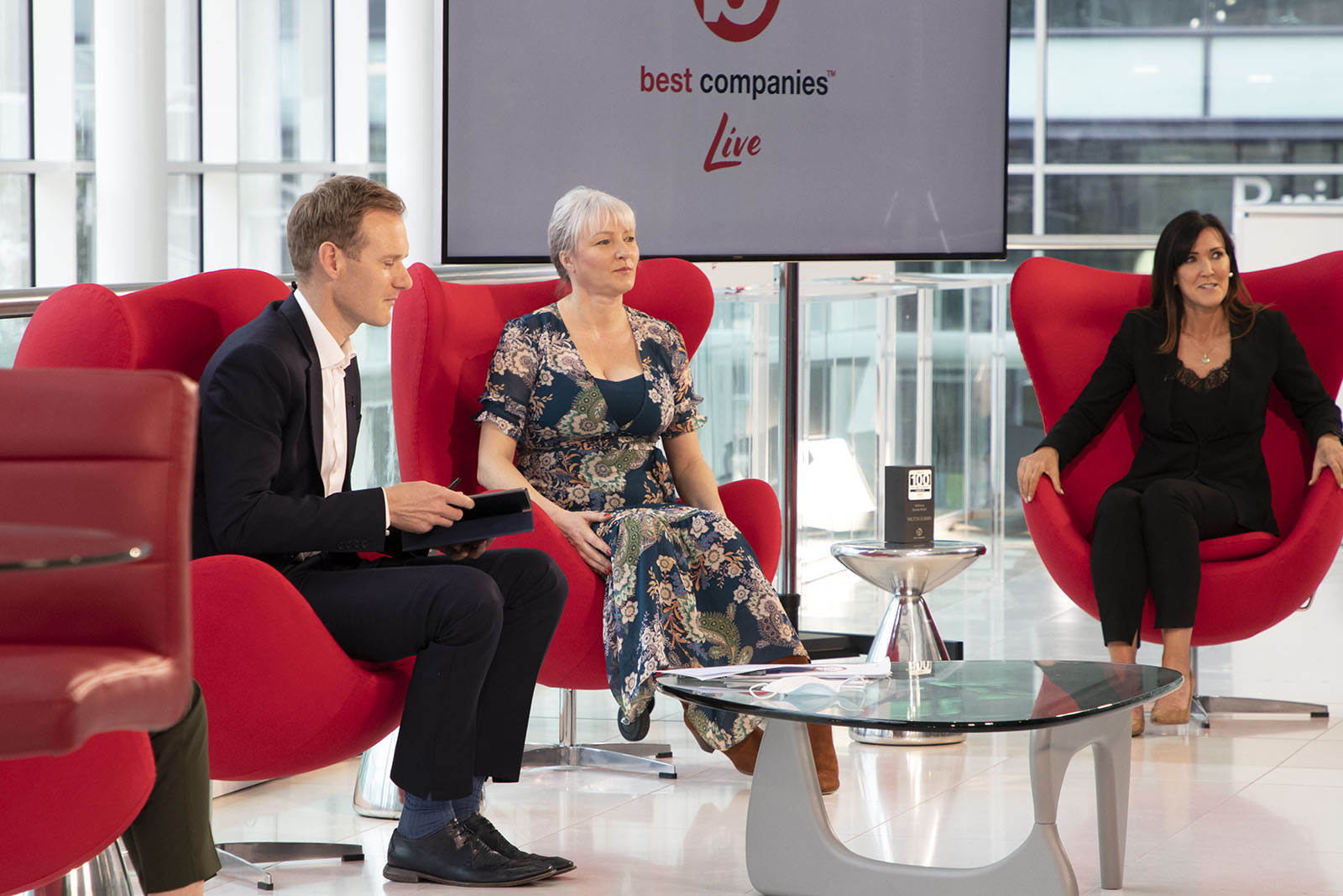 TV Presenter Dan Walker with Community Trust CEO Emma Ratzer MBE and People and brand Director of Wilton and Bain Claire Elliott on the set of Best Companies Live